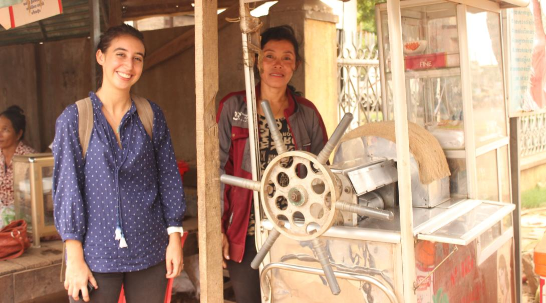 Projects Abroad volunteer visits a beneficiary who sells beverages in Cambodia.